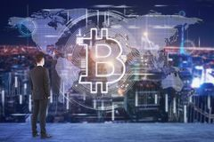 Cryptocurrency and e-commerce concept. Young businessman on rooftop looking at abstract bitcoin hologram. Cryptocurrency and e-commerce concept. Double exposure royalty free stock image
