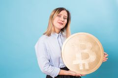 Cryptocurrency and economy concept - Young woman holds a gold bitcoin.  Stock Images