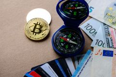 Cryptocurrency, electronic money and Hold your Money in Bitcoin. Concept. Virtual coins bitcoins, dollar and euro banknotes, credit cards on the table stock photography