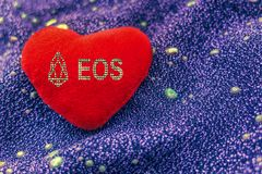 The cryptocurrency EOS symbol is a red plush heart with a neon background. Red plush heart with cryptocurrency EOS on neon background stock image