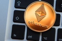 Cryptocurrency Ethereum coin on computer laptop keyboard. stock images