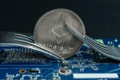 Cryptocurrency Ethereum ETH mit einer Gabel auf dem Motherboard lizenzfreie stockfotografie