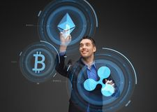 Businessman with cryptocurrency holograms. Cryptocurrency, financial technology and business concept - smiling businessman working with virtual bitcoin, ethereum Royalty Free Stock Image