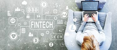 Cryptocurrency Fintech Theme with man using a laptop. In a modern gray chair stock photo