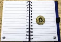 Cryptocurrency fizyczny złoty bitcoin Złoty bitcoin na notatnika tle zdjęcia royalty free