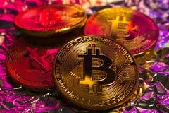 Cryptocurrency fysiskt guld- bitcoinmynt på färgrik bakgrund Arkivbilder