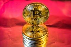 Cryptocurrency fysiskt guld- bitcoinmynt på färgrik bakgrund Arkivfoto