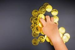 Cryptocurrency golden bitcoins coin in girl hand. Electronic vir Stock Photos