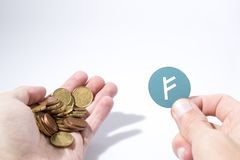 Cryptocurrency hand is holding euro coins and an auroracoin comp royalty free stock photography