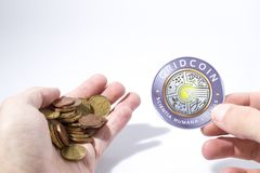 Cryptocurrency hand is holding euro coins and a gridcoin composition stock photo
