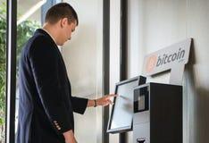 Cryptocurrency joven de la compra del hombre de negocios en la máquina del cajero automático para comprar y vender cryptocurrency foto de archivo