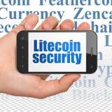 Cryptocurrency-Konzept: Übergeben Sie das Halten von Smartphone mit Litecoin-Sicherheit auf Anzeige Lizenzfreie Stockfotos