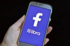 Cryptocurrency Libra pojęcie z ręki mienia telefonem komórkowym z Libra i Facebook logo na bue ekranie obraz stock