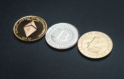 Cryptocurrency litecoin,Silver Bitcoin,Ethereum on black rough b Royalty Free Stock Photo