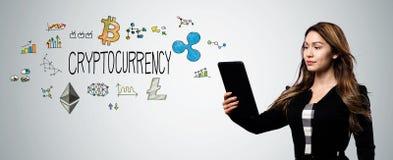 Cryptocurrency med kvinnan som rymmer en minnestavladator royaltyfria foton