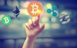 Cryptocurrency mit dem Handpressen ein Knopf Stockbilder