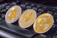 Cryptocurrency mynt över det svarta tangentbordet; Bitcoin Ethereum och Arkivfoto