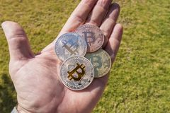 Cryptocurrency mynt i en hand; Bitcoin royaltyfri foto