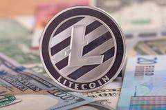 Cryptocurrency mynt Litycoin på euro- och dollarsedlarna Slut upp med den selektiva fokusen Arkivbild