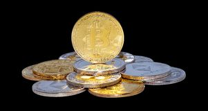 Mixed Crypto Currencies. Cryptocurrency physical gold bitcoin coin on bitcoins. Money concept stock photography