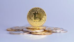 Mixed Crypto Currencies. Cryptocurrency physical gold bitcoin coin on bitcoins. Money concept royalty free stock image
