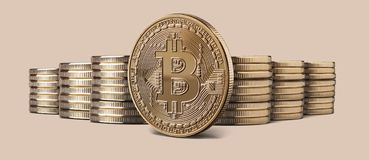 Cryptocurrency physical bitcoin gold coin and stacks of coins on backgound. Cryptocurrency physical gold bitcoin coin and Stacks of bitcoins standing against a stock photo