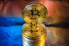 Cryptocurrency physical golden bitcoin coin on colorful backgrou Royalty Free Stock Photos