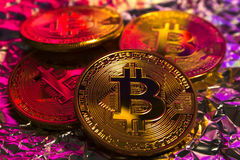 Cryptocurrency physical golden bitcoin coin on colorful background Stock Images