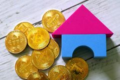 Cryptocurrency and property theme. Golden bitcoin replica with home model. Business and finance concept.  stock photography