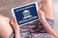 Cryptocurrency regulation concept on a tablet. Woman sitting on the floor with a tablet showing cryptocurrency regulation concept royalty free stock photo