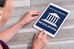 Cryptocurrency regulation concept on a tablet. Woman using a tablet showing cryptocurrency regulation concept royalty free stock photos