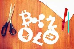 Cryptocurrency-Symbole werden von der Papierlüge auf einem hölzernen Schreibtisch herausgeschnitten Lizenzfreie Stockfotos