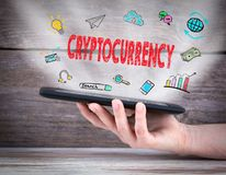 Cryptocurrency. Tablet computer in the hand. Old wooden background.  Stock Photos