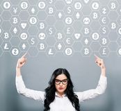 Cryptocurrency theme with business woman pointing upwards. On a gray background royalty free stock photos