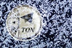 Cryptocurrency TON från telegram Silvermynttonen täckas med is royaltyfri foto