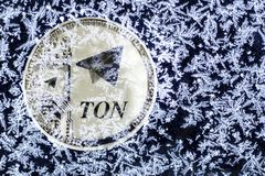 Cryptocurrency TON from telegram. Silver coin ton is covered with ice. royalty free stock photo