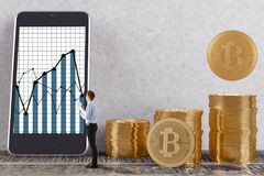Cryptocurrency and trade concept. Side view of young businessman in interior with golden bitcoin piles and business graph on smartphone screen. Cryptocurrency Royalty Free Stock Photos