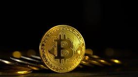 Cryptocurrency van het muntstukken virtuele geld bitcoin in de schemering op de achtergrond van goud bokeh Sluit omhoog stock footage