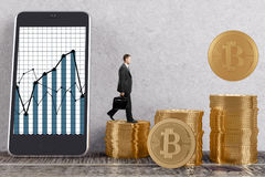 Cryptocurrency and virtual concept. Side view of young businessman in interior with golden bitcoin piles and business graph on smartphone screen. Cryptocurrency Royalty Free Stock Photos