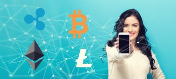 Cryptocurrency with young woman holding out a smartphone. In her hand stock image