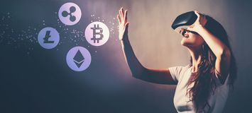 Cryptocurrency with woman using a virtual reality headset. Cryptocurrency with young woman using a virtual reality headset royalty free stock photography