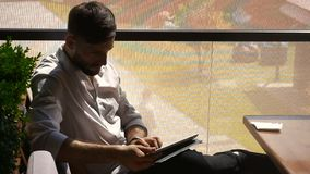 Cryptologist using tablet at cafe table and wipes sweat with tissue. Hardworking cryptologist working with tablet, thinking up password at cafe table near green stock footage