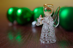 Crystal Angel on the background of Christmas balls. cristmas dec. Christmas balls on a wooden table.Crystal Angel on the background of  green Christmas balls,new Royalty Free Stock Image