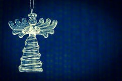 Crystal angel. Glass angel decoration against blue background royalty free stock photo