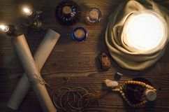 Crystal ball and ancient magic scrolls. Seance. Future reading concept. Crystal ball and ancient magic scrolls on fortune teller magic desk table background Stock Images