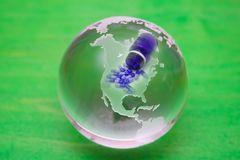 Crystal ball - blue pill spill. Crystal ball globe with blue pills spilling over North America. Green background stock photography