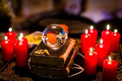 Crystal ball in the candle light to prophesy. Crystal ball to prophesy or esoteric clairvoyance during a Seance in the candle light Royalty Free Stock Photography