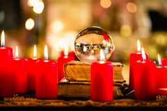 Crystal ball in the candle light to prophesy. Crystal ball to prophesy or esoteric clairvoyance during a Seance in the candle light Royalty Free Stock Image