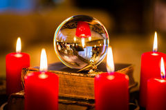 Crystal ball in the candle light to prophesy. Crystal ball to prophesy or esoteric clairvoyance during a Seance in the candle light Royalty Free Stock Photo
