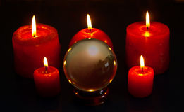 Crystal ball and candles. Crystal ball with image and five red candles burning Stock Photo